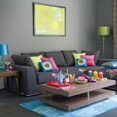 aménagement de salon avec un canapé gris housse en vert bleu et rose