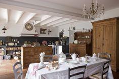 Une cuisine au style rustique et romantique, très lumineuse grâce à une baie vitrée.