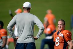 Denver Broncos quarterback Peyton Manning (18) stretches as he talks with Adam Gase during practice October 15, 2014 at Dove Valley. (Photo by John Leyba/The Denver Post)-- #ProFootballDenverBroncos