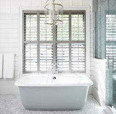 Stunning bathroom features a Round Edwardian Entry lantern suspended over a freestanding tub placed under windows dressed in plantation shutters alongside a grey marble tiled floor next to a shiplap and glass walk in shower. Green Shutters, Interior Shutters, Window Shutters, House Blinds, Bathroom Windows, Bathroom Inspiration, Bathroom Ideas, Bathroom Plans, Bathroom Pictures
