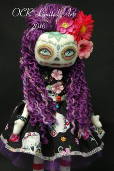 "~*~VIOLETTA~*~ Sugar Skull Art Doll, Dia de los Muertos-17.5""T dresses in black fabrics with sugar skull-flowers prints, silver color ribbon at front-black lace at collar. With purple tulle underskirt. Has black pantaloons-red stripe painted stocking .  Face is hand painted & sealed."