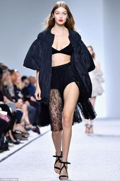 Sheer sass: Showing a serious amount of skin, the eldest Hadid sister made a head-turning appearance as she hit the runway in a plunging black bra and a sheer lace skirt