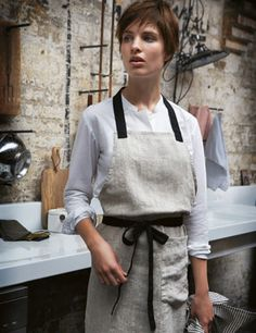 This is an ad for an apron (I think I can make it for less than $110 Canadian!) but I love the kitchen in the background: exposed brick, no upper cupboards, long, clean stretch of countertop - love!