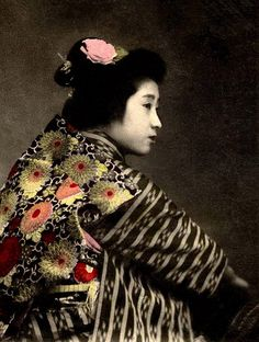 by Okinawa Soba, via Flickr.  This 100-year-old hand colored photo is by an unknown photographer.    Actually, it's a great image. The lighting, and her unique profile of a piercing gaze above her extended arm, gives a classic feel to the photo. Yet, the lines of the overwhelming obi that follow directly into her hair, and the high collar that erases all vestiges of a sensual nape of the neck (usually exposed by a low-slung kimono) makes this image anything but classical.
