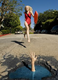 """Traffic watch: A beach lifeguard comes to the aid of a prosthetic hand"". Street #Art by artist Davide Luciano who transforms potholes into #StreetArt—after having crashed into one."