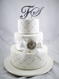 "A three tier White cake- with Strung diamantes- Silver cachous- A crystal Brooch- and all topped off with a ""full Bling"" set of Crystal Couture cake toppers. - http://cakethat.blogspot.co.uk/2010/10/hello-october.html#"