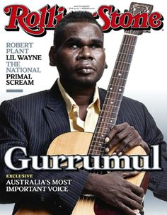 Gurrumul on the cover of Rolling Stone magazine (2011). Image description: cover of the Australian edition of Rolling Stone magazine featuring Geoffrey Gurrumul Yunupingu. Gurrumul is wearing a yellow shirt and striped suit jacket. He is holding a guitar to his chest, facing directly at the camera.