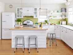 The kitchen has a distinctly retro feel with white laminate counters, schoolhouse pendants (from Pottery Barn), and a refrigerator and stove (both by Elmira Stove Works) that are new but reminiscent of 1950s-style appliances. To keep the room cheery, Sandy went with chartreuse glass tiles for the backsplash. Vintage glassware and other items that Sandy's collected stock the open shelves.