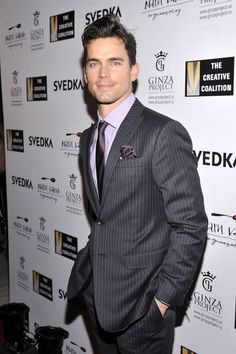 Matt Bomer in Alton Lane. Charcoal grey pinstripe suit, plum tie with lavender shirt and matching pocket square.