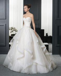 Vestido de organza royal y encaje pedrería con flor en color natural. 8A775- Chaqueta de tul sedoso bordado con pedrería en color natural.