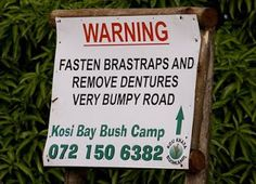 """Fasten your """"Bra-straps"""" ladies, bumpy road ahead! If you have dentures, please remove them too. (Signs in Africa). Funny Road Signs, Fun Signs, You Funny, Really Funny, Funny Stuff, Funny Things, Funny Photos, That Way, Home"""