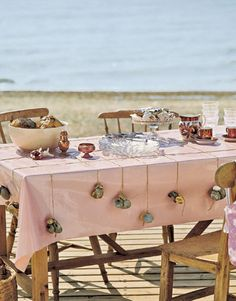 "Prevent tablecloths from billowing. Gather sun-bleached oyster or clam shells, sides still attached. Slip jute, knotted at both ends, between open ""wings"" of the shells, and lay across the table. For a centerpiece, gather turban shells and scallops."