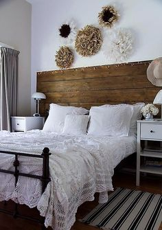 a welcoming farmhouse bedroom with a large wooden headboard, simple white nightstands, paper flowers over the bed for decor Bedroom Interior, Vintage Bedroom Decor, Bedroom Design, Farmhouse Bedroom Decor, Headboard Styles, Bedroom Vintage, Farmhouse Bedroom Set, Farmhouse Style Bedding, Remodel Bedroom