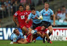 Michael Harris plaqué par Sarel Pretorius sous les yeux de Tom Carter, Ben Tapuai et Rob Horne lors de la rencontre entre les Waratahs et les Reds en Super Rugby