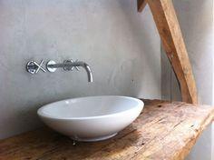 Eenvoud is zo mooi. Betonstuc wanden, oude houten planken, moderne kraan en een fris rond wasbakje voor het contrast.