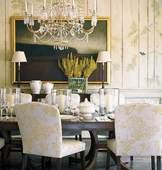 A dining room with painted wood panels.  I love the chandelier, chair & table, and table dressing!