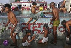 An Indian Sufi Muslim boy gives water to a man as he and others bathe at a makeshift camp before visiting the Ajmer Sharif during the Urs Festival in Ajmer, Rajasthan, Wednesday, May 23, 2012. AP / Kevin Frayer