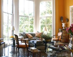 """Warm orange in the sitting room gives """"a cozy feel,"""" says Marshall, """"to what is a rather cold, grand space."""" He blended Benjamin Moore paints to get just the right color, which was inspired by the Hermès-box-orange leather of the Louis XV-style armchairs.   - HouseBeautiful.com"""