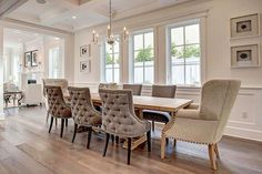 Elegant dining room features a George II Chandelier hung from a coffered ceiling over an extra long light wood trestle dining table flanked by gray velvet tufted dining chairs and facing light gray wingback captain's chairs placed in front of stacked wall art flanking three side-by-side windows.