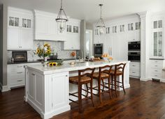 Country kitchen features white shaker cabinets paired with white marble countertops and mosaic marble tiled backsplash. Glass lanterns hang over kitchen island accented with lots of storage cabinets and sink lined with country barstools over rustic knotted wood floors. Wall of floor to ceiling kitchen cabinets surround pantry cabinets flanked by double ovens and built-in coffee machine atop convection oven.