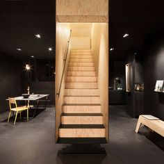 Hidden Fortress created a boxed-in floating staircase in the centre of this concept store, painting the outside black to contrast with the wood interior