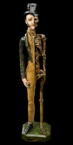 Coloured wax model of a male, half skeletal, half living and dressed in regency clothing, England, 1810-1850. Object description: This gentleman is dressed in Regency clothing typical of the first half of the 1800s. He is skilfully created out of wax. He is half man and half skeleton. The statue may have been made for one of three reasons: a darkly comic novelty, a 'memento mori' (a reminder of death), or a teaching aid.