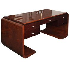 A stunning modernist desk made in Milan during the 1930's. The desk is made of rosewood, burl, and five stained oak wood drawers with sturdy chrome handles. The table legs are very unusual in form, but overall great quality.