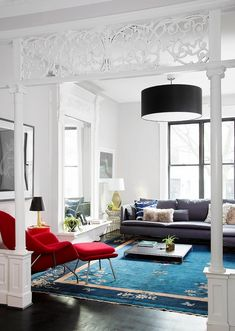 Living room with a large area rug, a modern black light, and a red accent chair