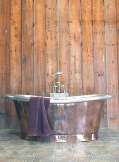 Love this big copper tub with barnwood walls