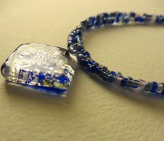 Conjure up images of deep, sapphire blue seas and an endless Mediterranean summer.  This hand made two-strand bracelet is made with delicate 10/0 size beads ranging from dark navy to pale cerulean in color to reflect the many different shades of the sea.  A beautiful Murano artisan glass pend...