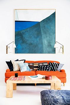 Modern living room wit contemporary art, a bright orange sofa, and printed throw pillows