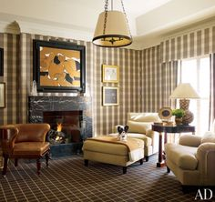 Sheathed in a Schumacher plaid, the upper lounge in J. Randall Power's house features a large Conrad Marca-Relli collage and a circa-1900 leather-clad English games chair; Millicent, a papillon, rests on an Hermès throw.