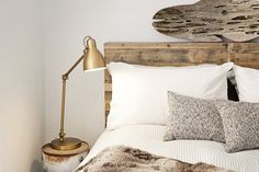 Jesse's Modern Bachelor Pad. Love this interplay of textures and patterns between the shiny brass bedside task table lamp, fur throw, striped duvet, textured throw pillows, driftwood art fish and reclaimed wood headboard.
