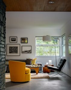 In the living room, the architects painted the limestone fireplace a dark shade of blue-green. The walnut coffee table is by Noguchi for Herman Miller. The Barcelona chair is by Mies van der Rohe.