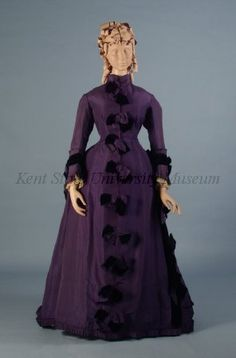 ~Dress Date1875-1879 CultureAmerican DescriptionPurple silk taffeta. Stand up collar, cuffs with pleated taffeta and velvet, skirt with train.  Original catalog card: L. 1870s, Purple silk taffeta dress. The dress with stand-up collar and front bows of taffeta and velvet. The cuffs with pleated taffeta and band of navy velvet. At the right side a pleated fan shape pocket. The back with bows and piped taffeta in interlacing pattern, and a train~
