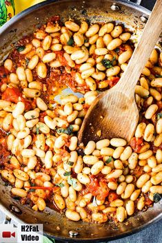Sautéed white beans with garlic and sage in a large skillet with wooden spoon