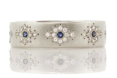 The diamond and blue sapphire pattern around the circumference of this band is playful, but elegant.
