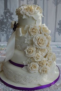 Ivory and champagne wedding cake  cascading roses with cadburys purple trimming