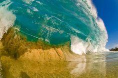 Vague turquoise et mouvement du sable par Clark Little