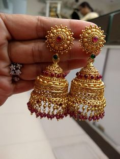 Traditional & Temple Jhumkas/Earrings(Screw Style) in Silver and Gold Polish with Rubys and Emeralds - Indian Temple Jewelry for Special Occasions, Pooja Ceremonies, Festival Celebrations - Bridal Jewelry Weight : gms Estimated shipping delivery times: Gold Jhumka Earrings, Jewelry Design Earrings, Gold Earrings Designs, Gold Jewellery Design, Gold Jewelry, Fancy Jewellery, Antique Earrings, Etsy Earrings, Gold Necklace
