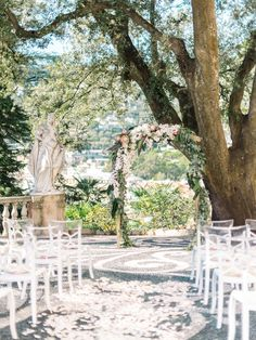 An absolutely stunning outdoor venue, complete with statue and floral arch.