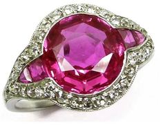 Burmese pink sapphire and diamond cluster ring. Made by Cartier in 1910, this ring is centered by a round faceted Burmese pink sapphire of approx 3.20 ct, flanked by tapered calibre cut pink sapphires. Surrounding that glorious center of pink sapphires are diamonds, millegrain-set in platinum.