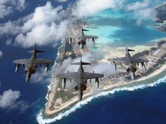 Four USMC AV-8B Harrier IIs fly in formation over Wake Island Airfield in the Pacific.