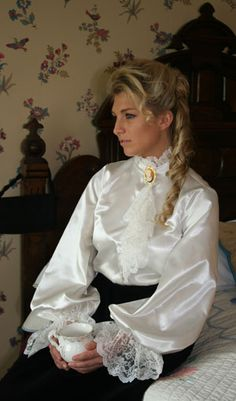 Price: $89.95  What could be more romantic and feminine than shimmering satin and frothy lace? The satin blouse, available in your choice of colors, features an attached lace trimmed jabot and closes with satin-covered buttons, and very full long sleeves with a deep ruffle of lace at the cuff.