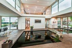 Der trendige Teich im Interieur dieses Wohnzimmer wirkt modern und besitzt eine Brücke