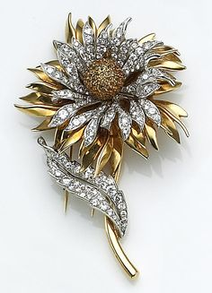 A diamond, yellow sapphire and eighteen karat gold flower brooch, Tiffany & Co. of flower motif, centering a bombé form set throughout with round facet-cut yellow sapphires, encircled by diamond-set and polished gold petals, the leaf set with round brilliant-cut diamonds; signed Tiffany & Co