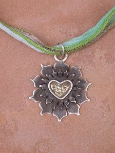 Beautiful lotus flower pendant made from sterling silver with silver wire heart shaped detail and inlaid with 14k gold.  By Karen Luther Jewelry (available on etsy).