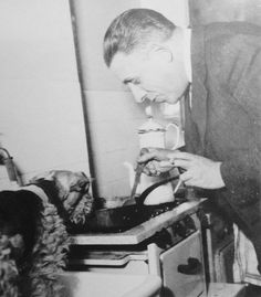 Francis Poulenc having a smoke while cooking dinner with his dog.