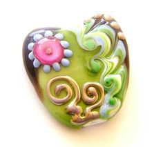 This heart focal bead has base in white encase with transparent purple and green then decorated with dots, swirled