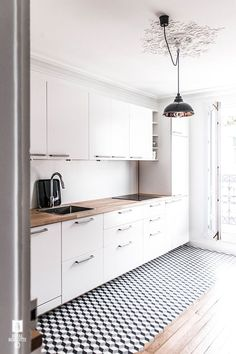 Interiors | Paris Apartment // minimalist white kitchen with butcher block counter tops, gorgeous black and white floor tile and modern light fixture